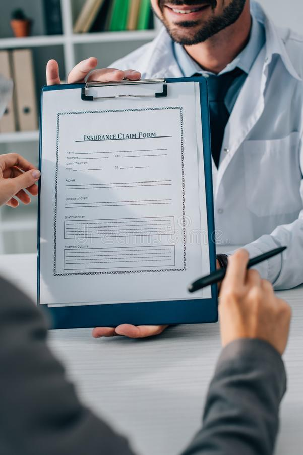 Cropped image of doctor showing insurance claim form to patient. In clinic stock photos