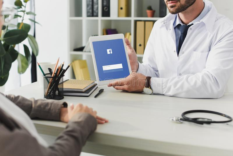 Cropped image of doctor showing tablet with loaded facebook page to patient. In clinic royalty free stock photography