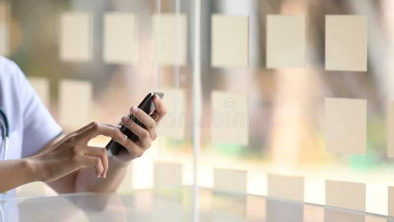Cropped image of doctor using mobile phone royalty free stock photos