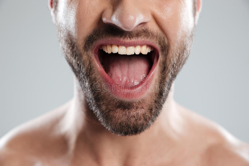 Cropped image of excited mans half face with naked shoulders. Cropped image of an excited bearded mans half face with naked shoulders and open mouth isolated stock photography