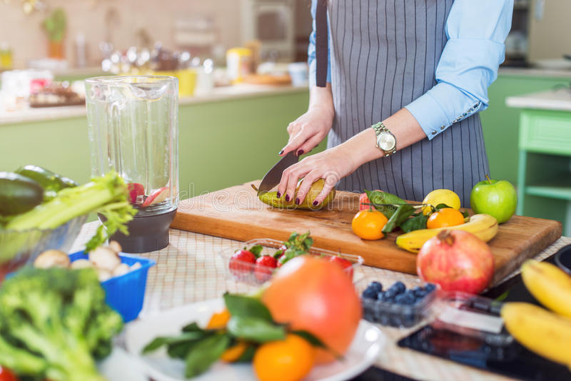 Cropped image of female cook cutting fruit on board preparing smoothie in kitchen royalty free stock photography