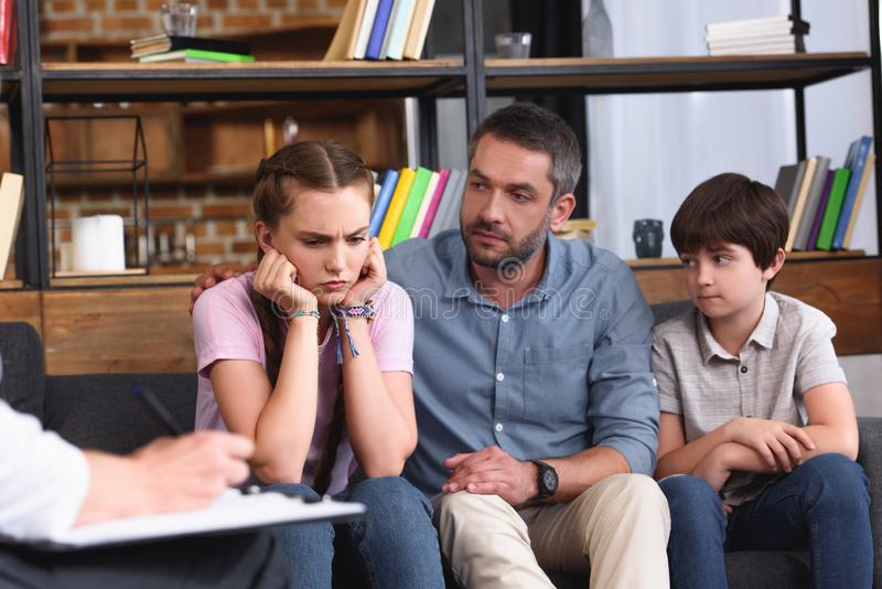 Cropped image of female counselor writing in clipboard while man. Cropped image of female counselor writing in clipboard while men cheering up angry daughter on royalty free stock images