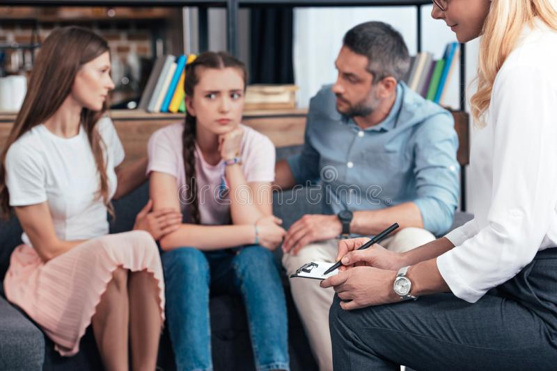 Cropped image of female counselor writing in clipboard while parents cheering up daughter. On therapy session stock photo