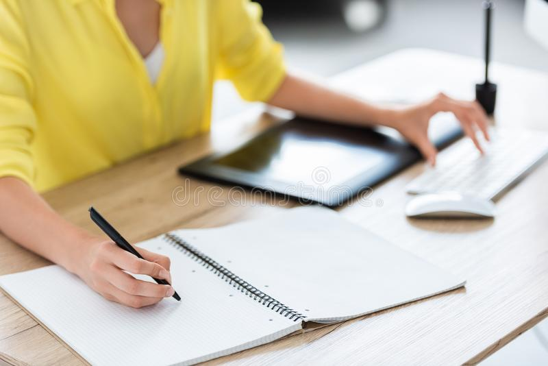 Cropped image of female freelancer writing in textbook and working on computer. At home office royalty free stock photo