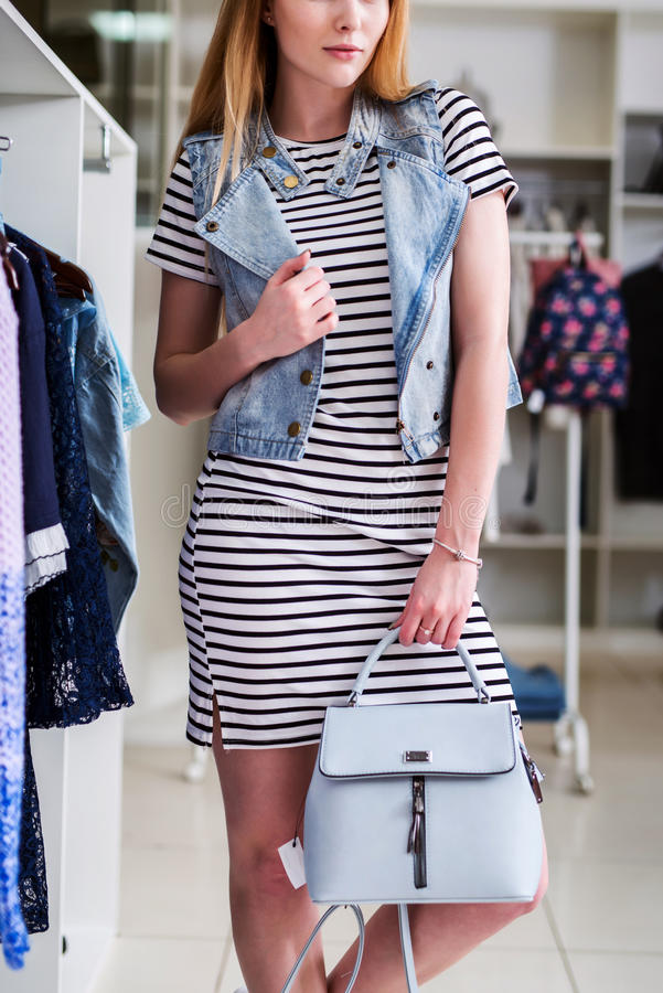 Cropped image of female model wearing striped dress, denim vest and handbag from summer collection in a fashion boutique royalty free stock photography