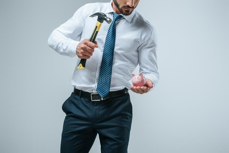 cropped image of financier breaking piggy bank with hammer stock photography
