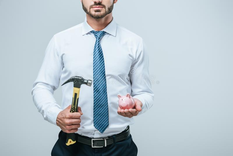 Cropped image of financier standing with piggy bank and hammer. Isolated on grey royalty free stock image