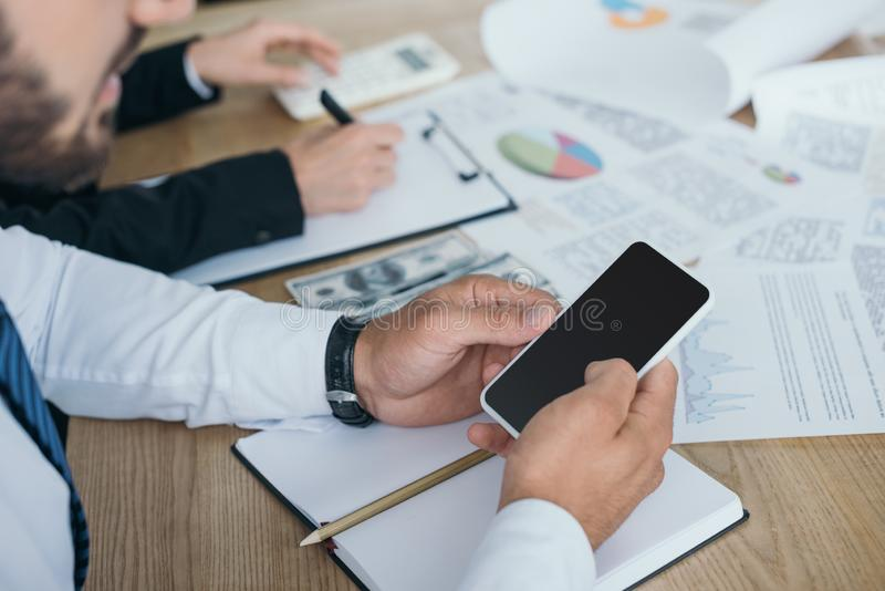 Cropped image of financier using smartphone. In office royalty free stock photos