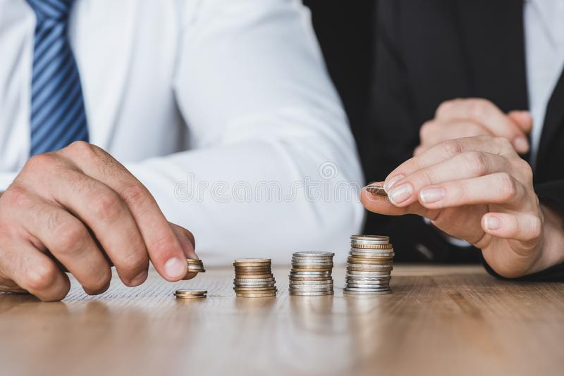 Cropped image of financiers stacking coins on table. In office stock photos