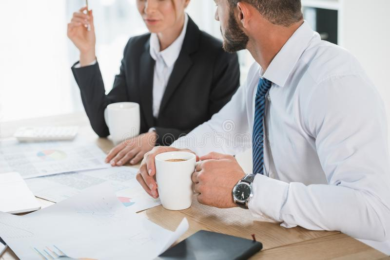Cropped image of financiers working with documents during coffee break. In office stock image