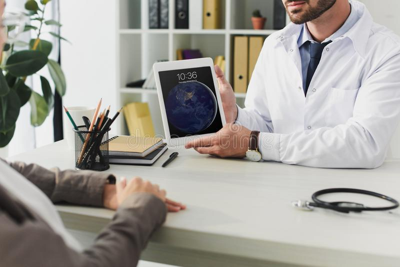 Cropped image of general practitioner showing patient ipad. In clinic royalty free stock images