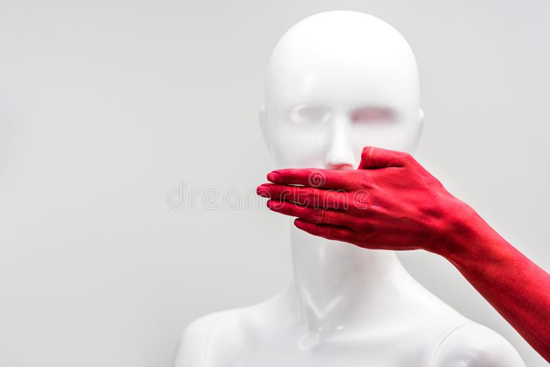 Cropped image of girl in red paint covering mannequin mouth with hand. Isolated on white royalty free stock photo