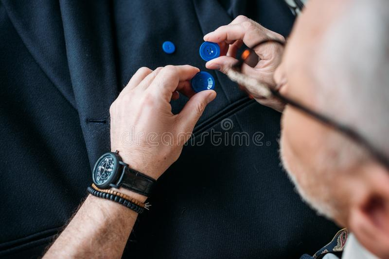 Cropped image of grey hair tailor choosing buttons. At sewing workshop royalty free stock image