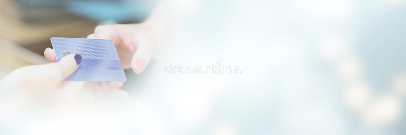 Cropped image of hand handing over credit card. At counter of shop royalty free stock images