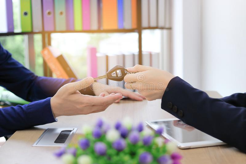 Cropped image of hands of sales car dealership giving keys to customer.  stock photos