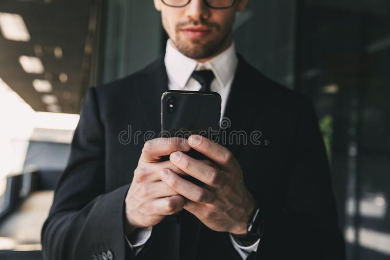 Handsome business man near business center using mobile phone. Cropped image of handsome business man near business center using mobile phone stock photography
