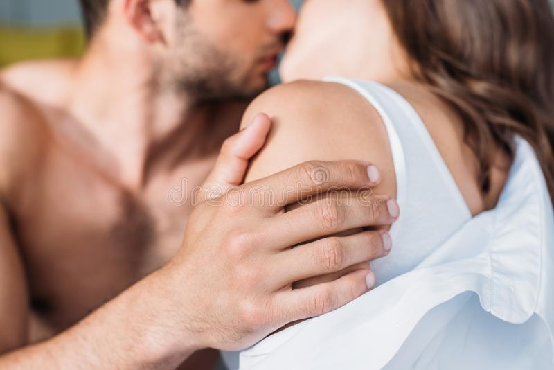 Cropped image of heterosexual couple hugging and kissing. At home royalty free stock photo