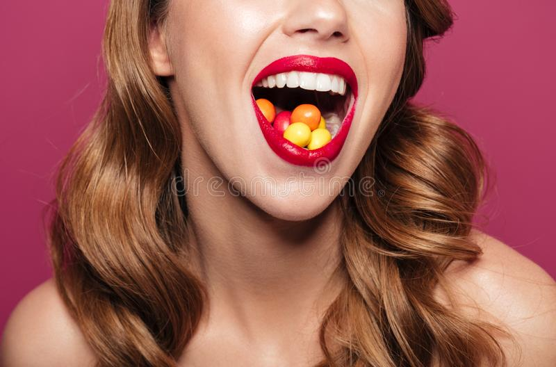 Cropped image of lady holding candies in her mouth ans smiling isolated stock photos