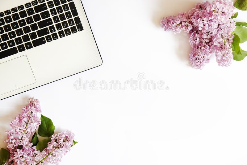 Top view of female worker desktop with laptop, flowers and different office supplies items. Feminine creative design workspace. stock photography