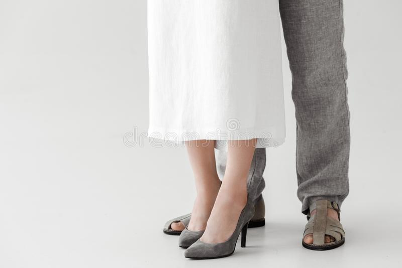 Cropped image of legs of couple of models in linen dress and trousers. Isolated on grey background stock photo