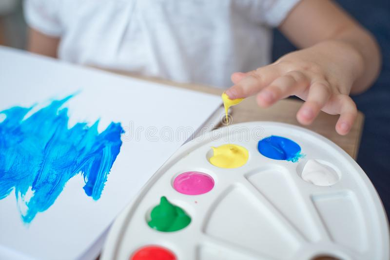 Cropped image of little girl playing with paints royalty free stock images