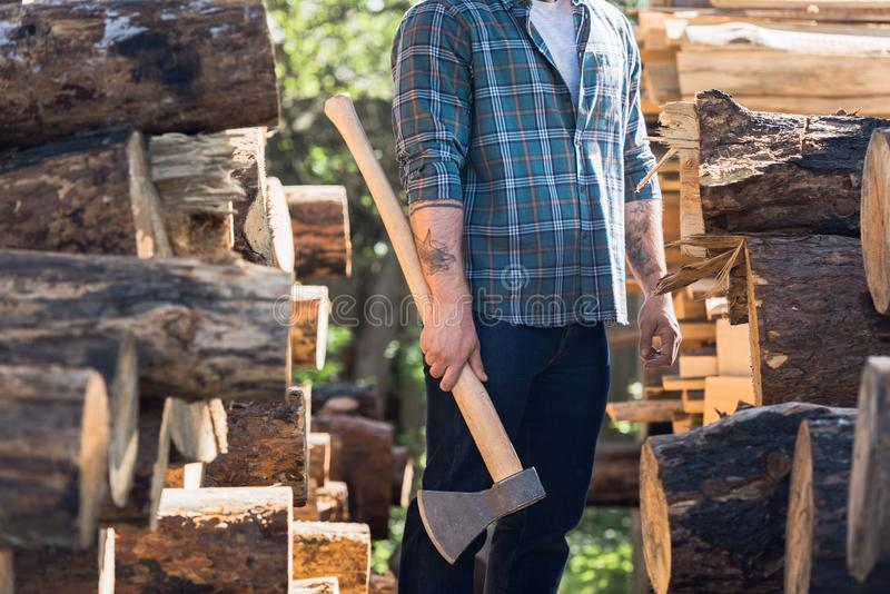 cropped image of lumberjack in checkered shirt with tattooed hands holding axe between logs at sawmill stock images