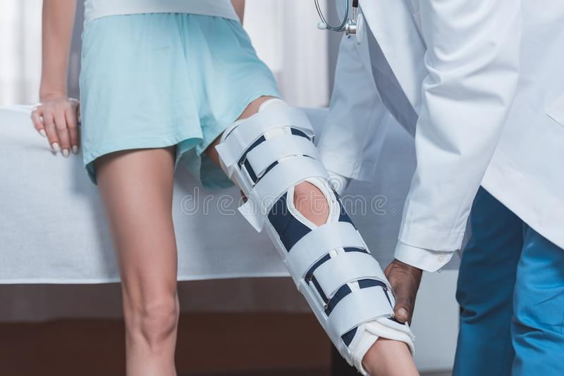 Cropped image of male african american doctor examining female patient leg royalty free stock image