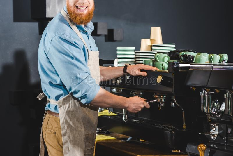 Cropped image of male barista in apron using coffee. Machine stock photos