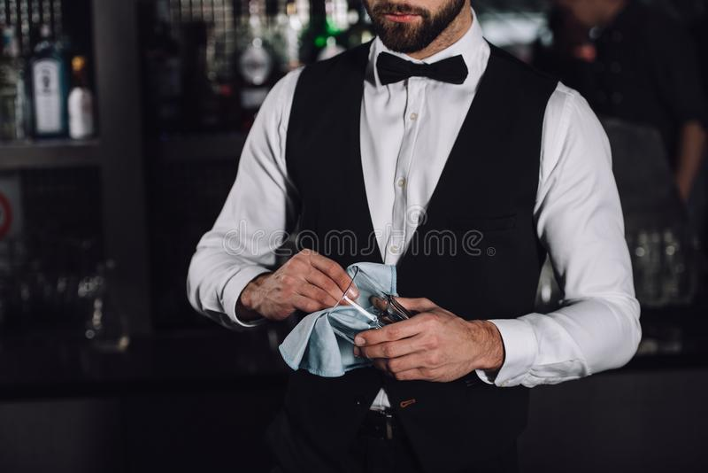 cropped image of male bartender cleaning glass with rag royalty free stock images