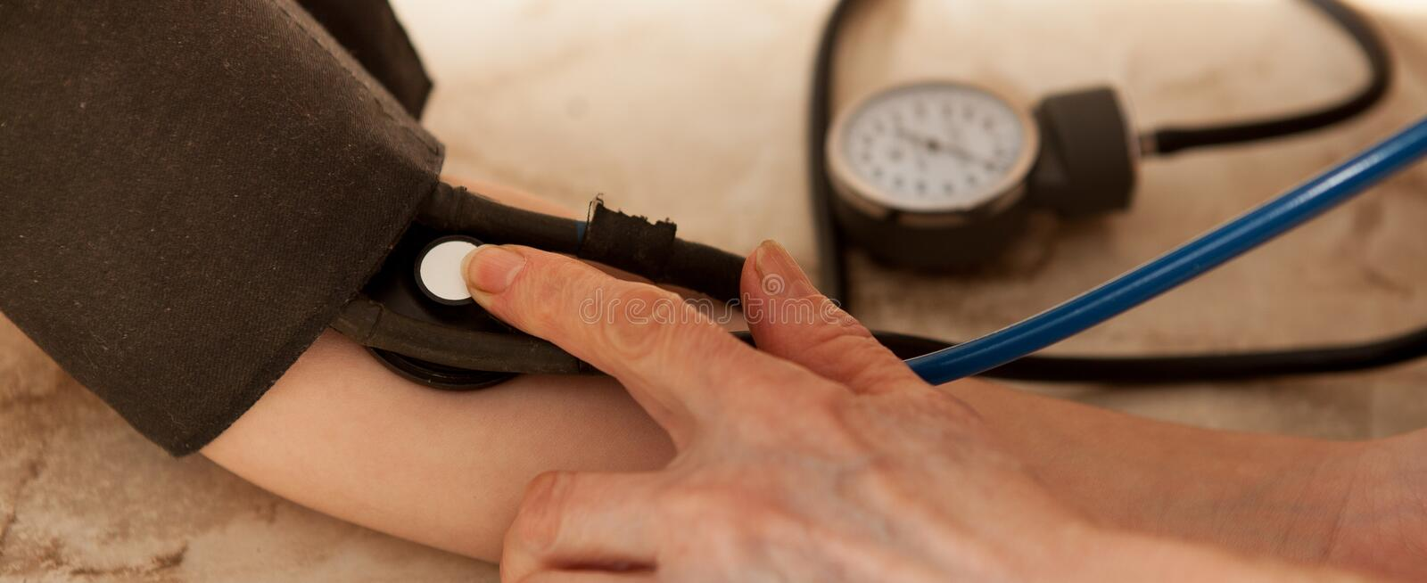 Cropped image of male doctor checking blood pressure of patient at table stock photos