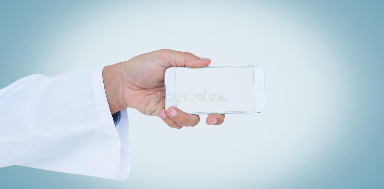 Male doctor holding smart phone with blank screen. Cropped image of male doctor holding smart phone with blank screen against white background royalty free stock photography