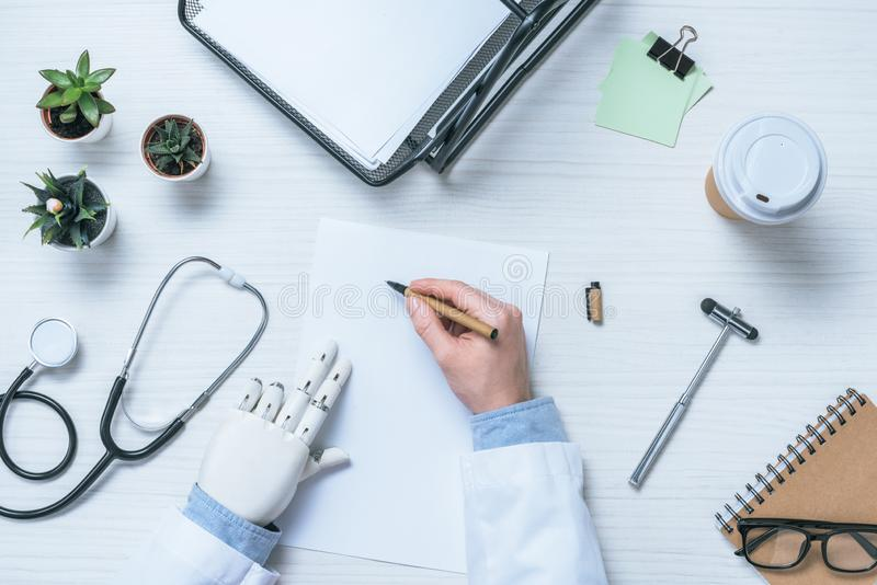 cropped image of male doctor with prosthetic arm writing on blank paper at table with reflex hammer stethoscope and coffee stock photos