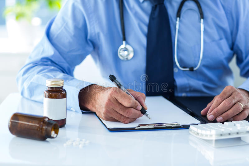 Cropped image of male doctor writing document in hospital stock photos