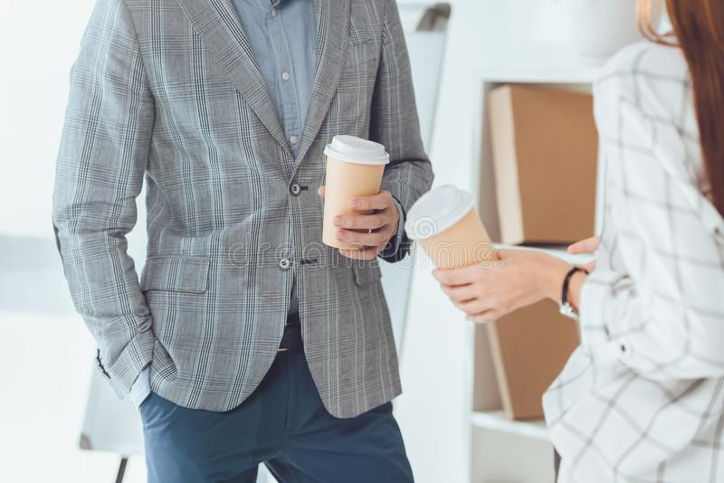 Cropped image of male and female colleagues having coffee break. In office stock photos