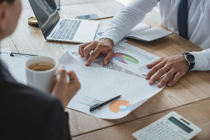 Cropped image of male and female financiers working with documents. In office royalty free stock photo
