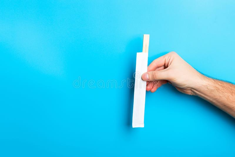 Cropped image of male hand showing chopsticks on blue background. Asian food concept with copy space stock images