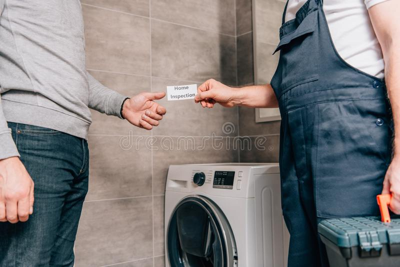 Cropped image of male handyman giving card with lettering home inspection to owner. In bathroom royalty free stock photos