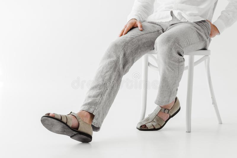 cropped image of male model in linen clothes sitting on chair royalty free stock photo