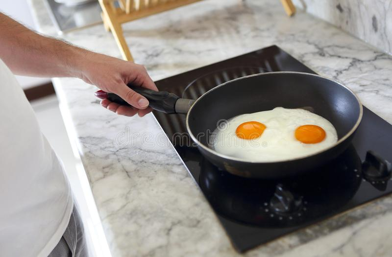 Cropped image of man cooking scrambled eggs on frying pan stock photo