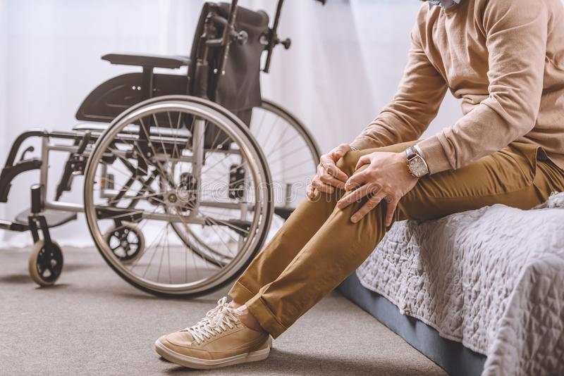 Cropped image of man with disability sitting on bed and touching legs stock photos