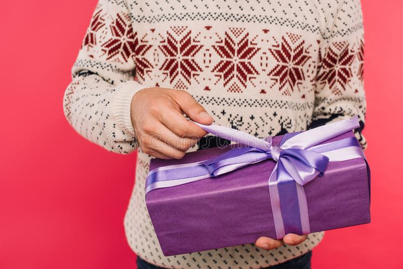 Cropped image of man opening gift box. Isolated on pink royalty free stock image