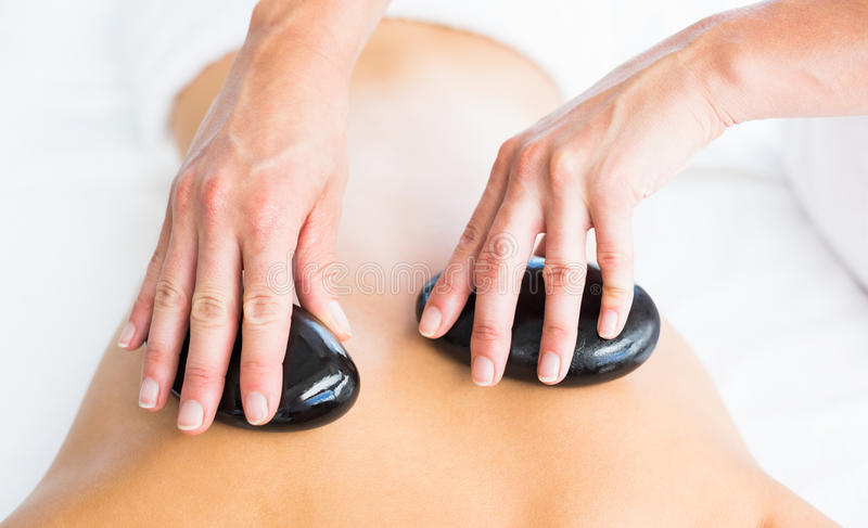 Cropped image of masseur giving hot stone massage on woman back. At spa royalty free stock photo