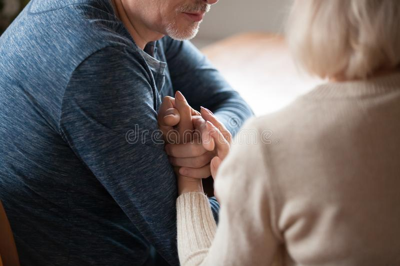 Cropped image mature man holding hand of loving woman royalty free stock photography