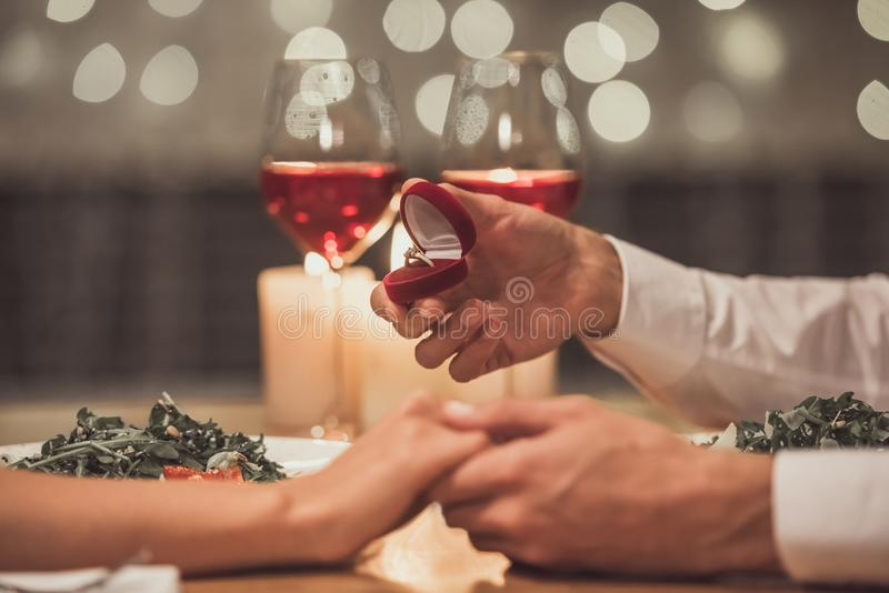 Man proposing in restaurant. Cropped image of men holding an engagement ring and proposing to his girlfriend in a restaurant royalty free stock image