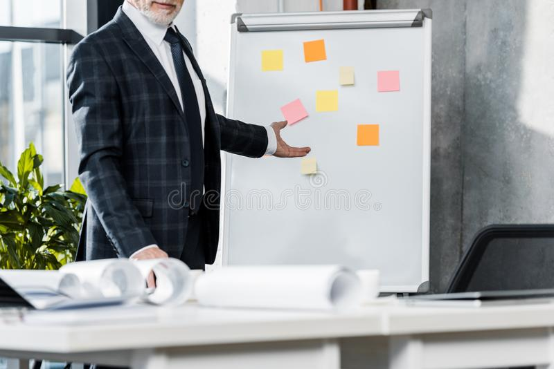 Cropped image of middle aged businessman pointing on flipchart. In office royalty free stock images