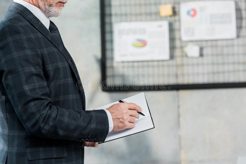Cropped image of middle aged businessman in suit writing something to notebook. In office royalty free stock image