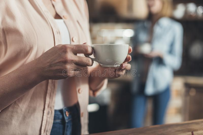 Cropped image, middle section of person holding coffee cup, standing stock image