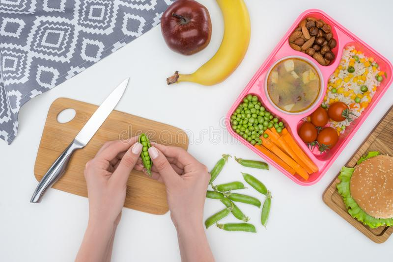 cropped image of mother preparing kids dinner for school and holding green peas stock image