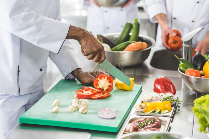 Cropped image of multicultural chefs cutting and washing vegetables. At restaurant kitchen royalty free stock image