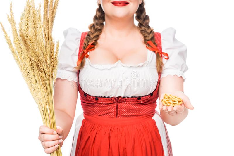 cropped image of oktoberfest waitress in traditional german dress showing little pretzels and holding wheat stock photos